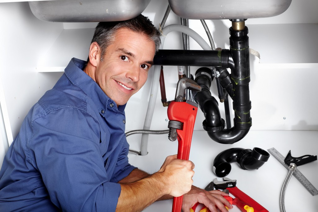 Plumber under the sink with tools