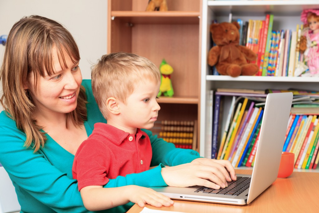 child and mother with laptop