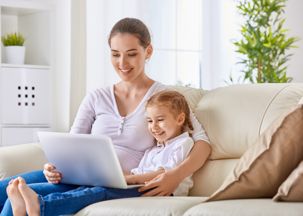 kid and mother looking at laptop screen