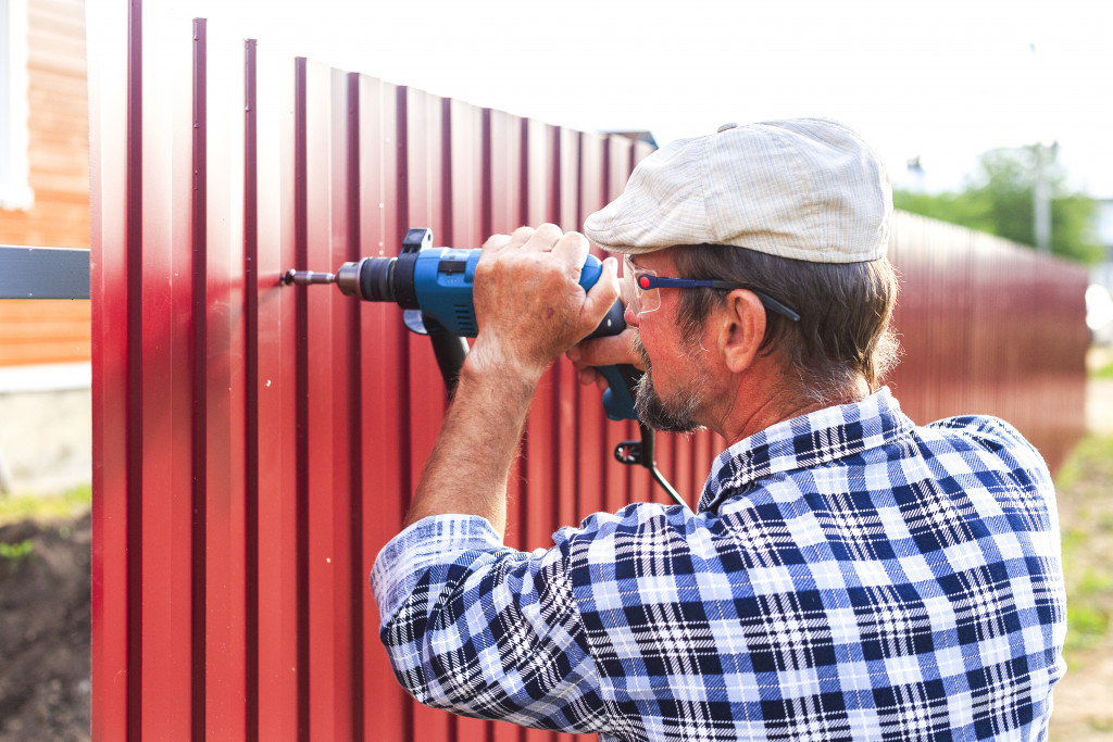 elderly man with a drill building a fence