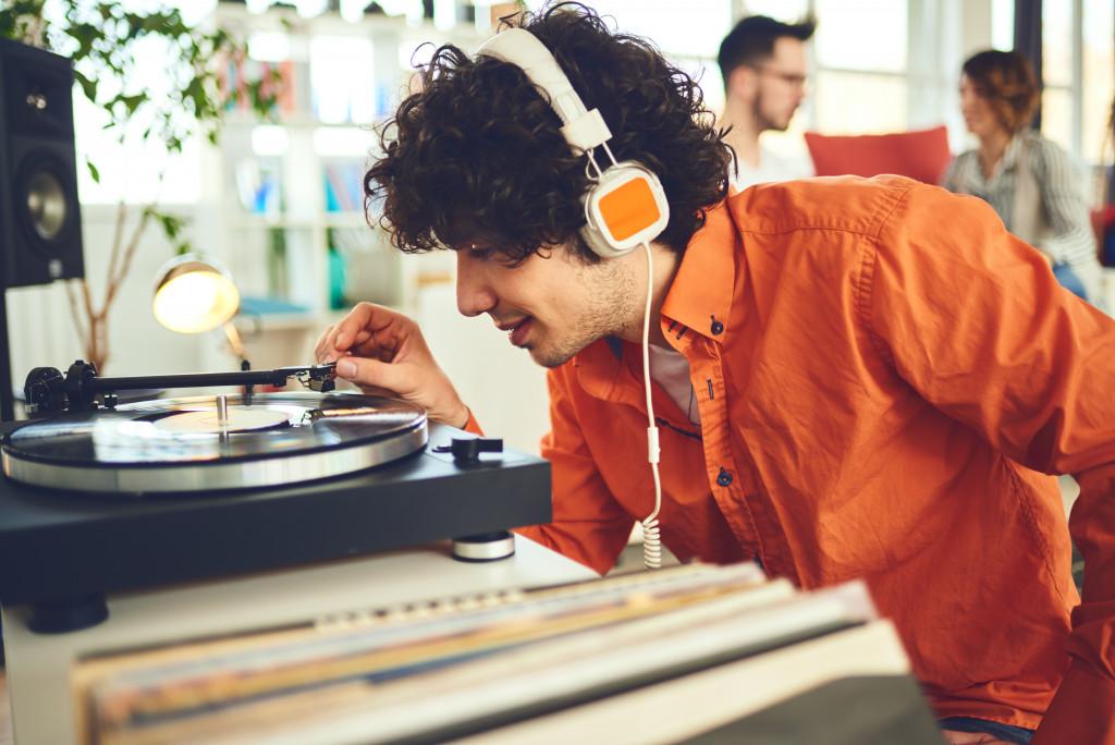 man listening to vinyl record player